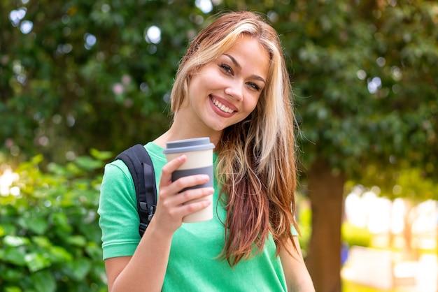 Молодая студентка женщина на открытом воздухе с счастливым выражением лица