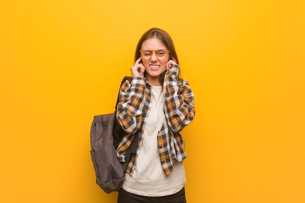 手で耳を覆う若い学生女性