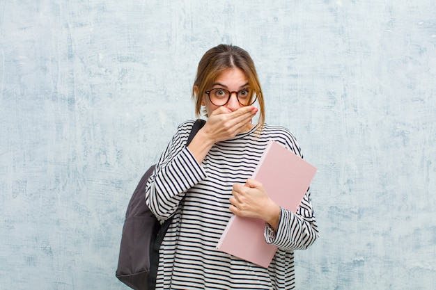 Young student woman covering mouth with hands with a shocked, surprised expression, keeping a secret or saying oops