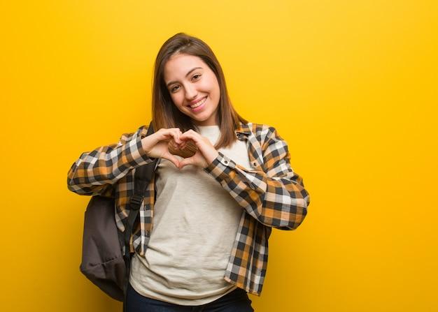 Молодая женщина студента делая форму сердца с руками