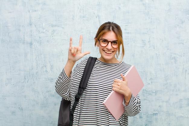 Молодой студент женщина чувствует себя счастливым, веселым, уверенным, позитивным и мятежным, делая знак рок или хэви-метал рукой