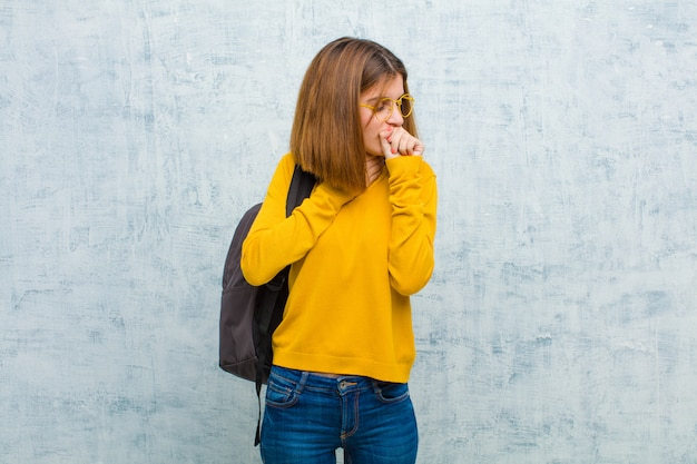 Young student woman feeling ill with a sore throat and flu symptoms, coughing with mouth covered against grunge wall wall