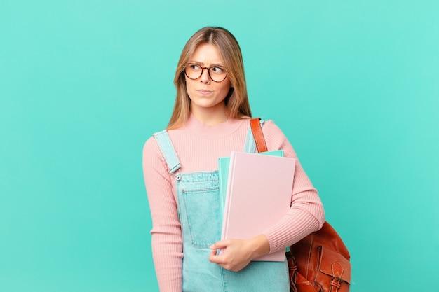 Молодая студентка чувствует себя грустной, расстроенной или сердитой и смотрит в сторону