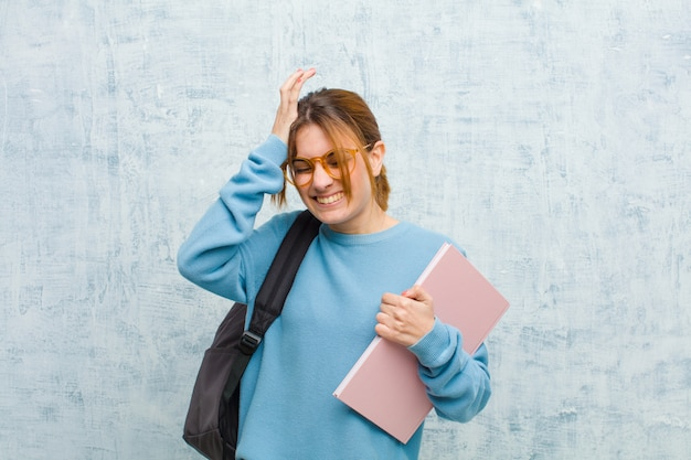 Young student woman feeling stressed and anxious, depressed and frustrated with a headache, raising both hands to head