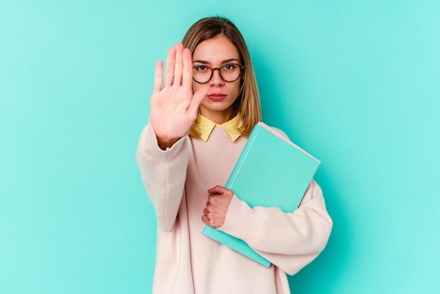 一時停止の標識を示す伸ばした手で立っている青い背景で隔離の本を保持している若い学生女性は、あなたを防ぎます。