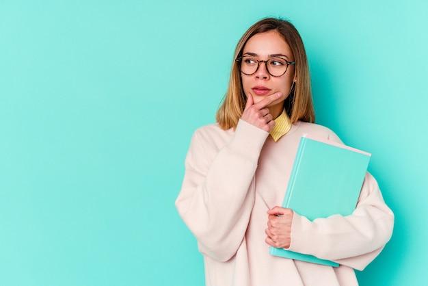 Молодая студентка женщина, держащая книги, изолированные на синем, глядя в сторону с сомнительным и скептическим выражением.