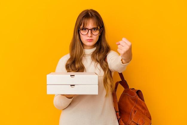 Молодая студентка держит пиццу над изолированной стеной, показывая кулак вперед, агрессивное выражение лица