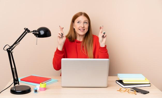 Молодой студент женщина на рабочем месте с ноутбуком с пальцами пересечения и желая лучшего