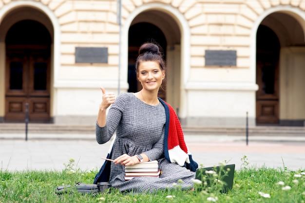 Молодой студент женщина показывает палец вверх возле университета.