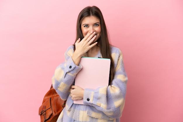 Молодая студентка изолировала счастливую и улыбающуюся, прикрывая рот рукой