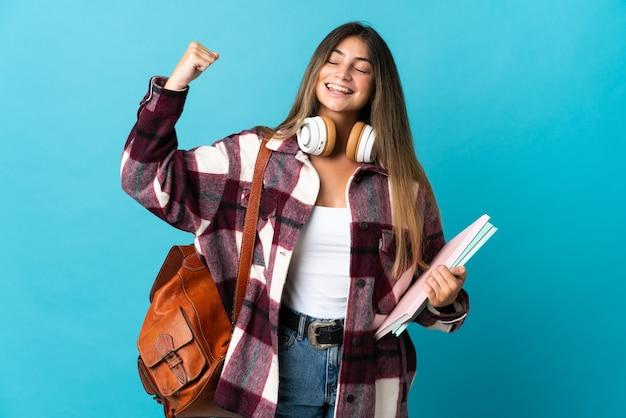 強いジェスチャーをしている青い壁に孤立した若い学生女性