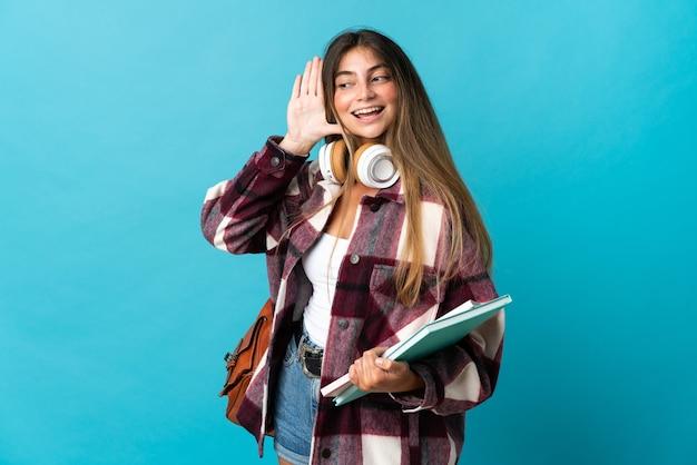귀에 손을 넣어 뭔가를 듣고 파란색 벽에 고립 된 젊은 학생 여자