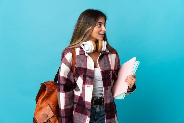 側面を見て青い壁に孤立した若い学生女性