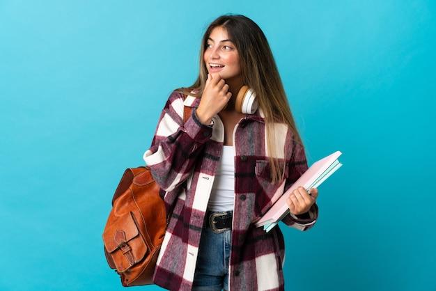 横を見て笑っている青い壁に孤立した若い学生女性