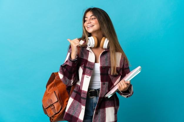 製品を提示する側を指している青い壁に分離された若い学生女性