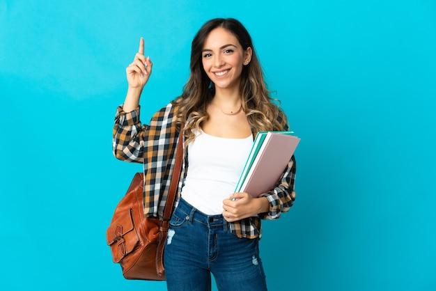 좋은 아이디어를 가리키는 파란색 벽에 고립 된 젊은 학생 여자