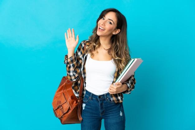 幸せな表情で手で敬礼青い壁に孤立した若い学生女性