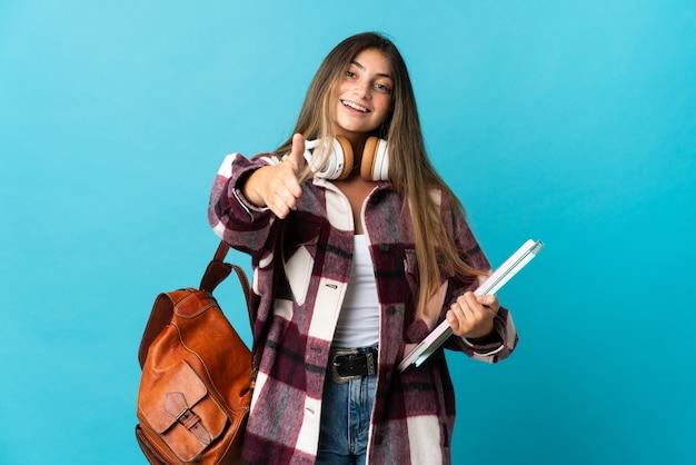 좋은 거래를 닫기 위해 악수하는 파란색 벽에 고립 된 젊은 학생 여자