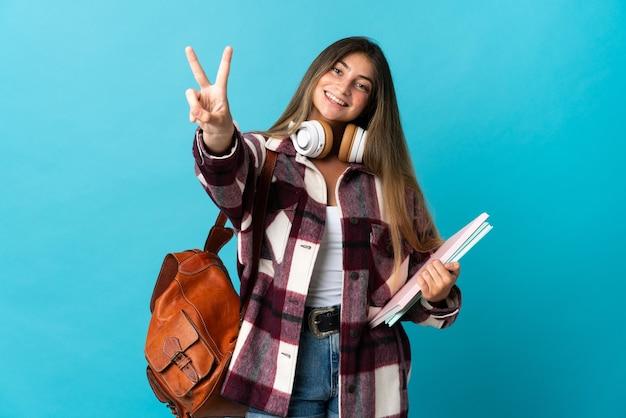 笑顔と勝利のサインを示す青い壁に孤立した若い学生女性