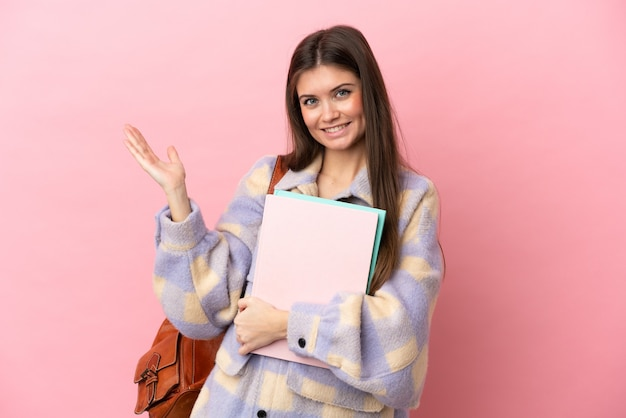 ピンクの背景に孤立した若い学生女性が手を横に伸ばして来るように誘う