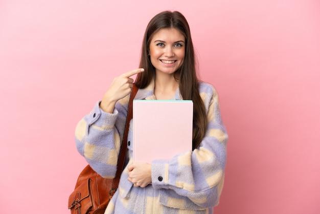 제스처를 엄지 손가락을주는 분홍색 배경에 고립 된 젊은 학생 여자