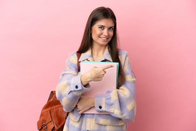 Молодая студентка женщина изолирована на розовом фоне, указывая назад