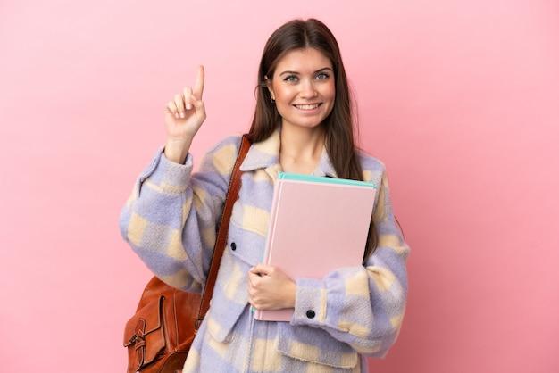 좋은 아이디어를 가리키는 분홍색 배경에 고립 된 젊은 학생 여자