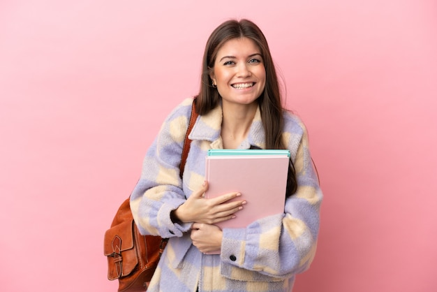 많이 웃 고 분홍색 배경에 고립 된 젊은 학생 여자