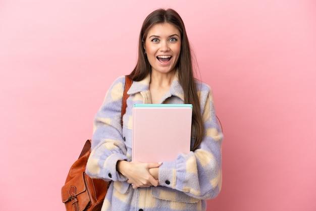 놀라운 표정과 분홍색 배경에 고립 된 젊은 학생 여자