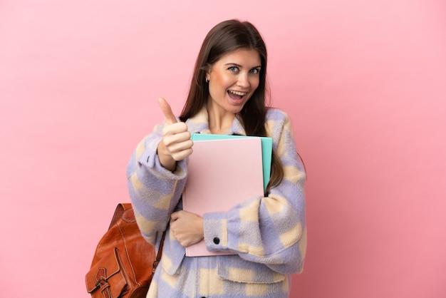 좋은 일이 일어났기 때문에 엄지 손가락으로 분홍색 배경에 고립 된 젊은 학생 여자