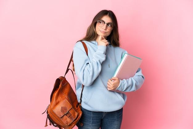 의심과 생각을 갖는 분홍색에 고립 된 젊은 학생 여자