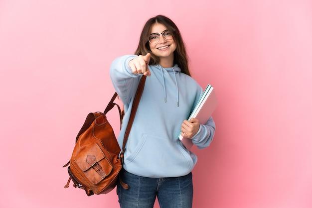 행복 한 표정으로 핑크 포인팅 앞에 고립 된 젊은 학생 여자