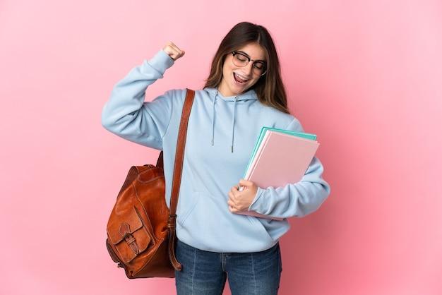 강한 제스처를 하 고 분홍색 벽에 고립 된 젊은 학생 여자