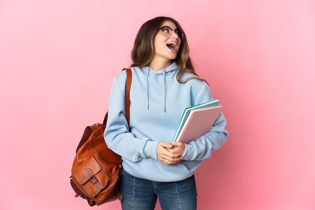 분홍색 벽 웃음에 고립 된 젊은 학생 여자