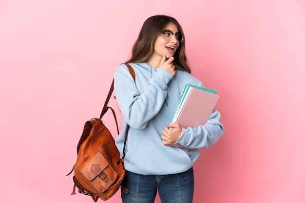 측면을 찾고 웃 고 분홍색 벽에 고립 된 젊은 학생 여자