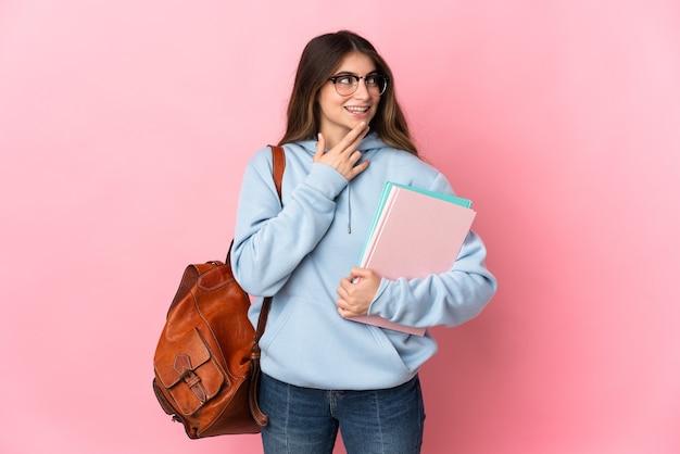웃는 동안 올려 분홍색 벽에 고립 된 젊은 학생 여자