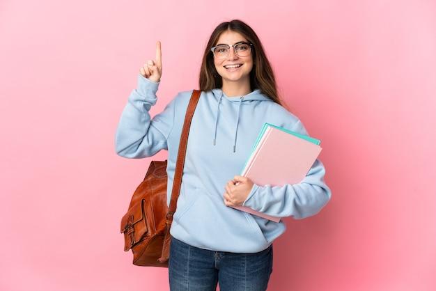 좋은 아이디어를 가리키는 분홍색 벽에 고립 된 젊은 학생 여자