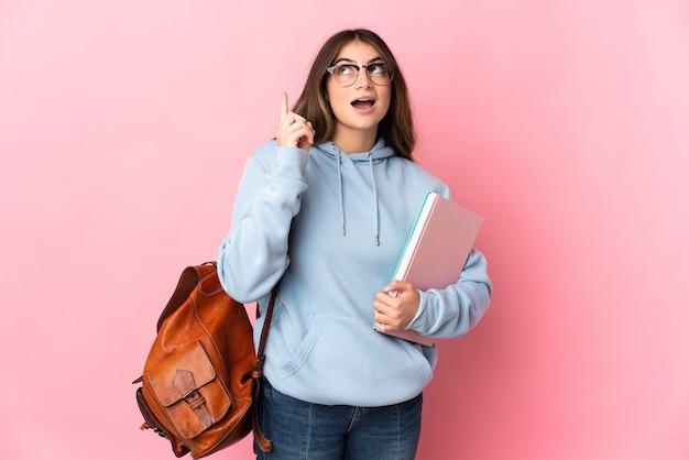 손가락을 가리키는 아이디어를 생각하는 분홍색 벽에 고립 된 젊은 학생 여자