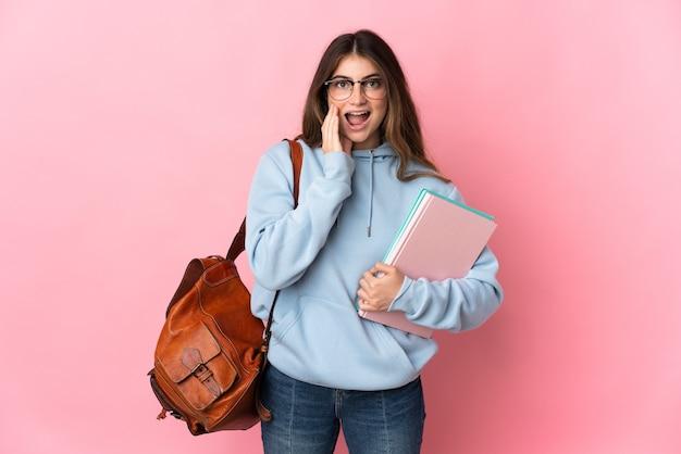 놀람과 충격 된 표정으로 분홍색 벽에 고립 된 젊은 학생 여자