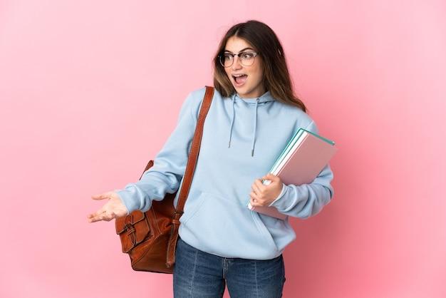 측면을 보는 동안 놀라운 표정으로 분홍색 벽에 고립 된 젊은 학생 여자
