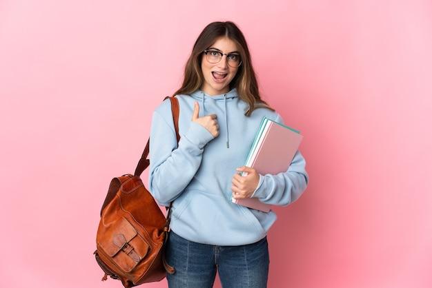 驚きの表情でピンクに分離された若い学生女性