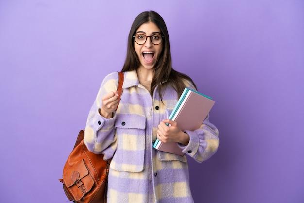 우승자 위치에서 승리를 축하하는 보라색 배경에 고립 된 젊은 학생 여자