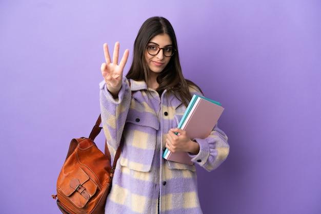幸せな紫色の背景に分離された若い学生女性と指で3を数える