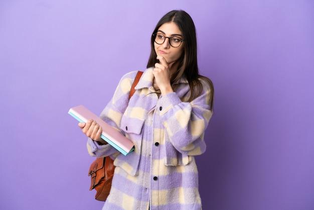 Молодая студентка женщина изолирована на фиолетовом фоне с сомнениями и мышлением