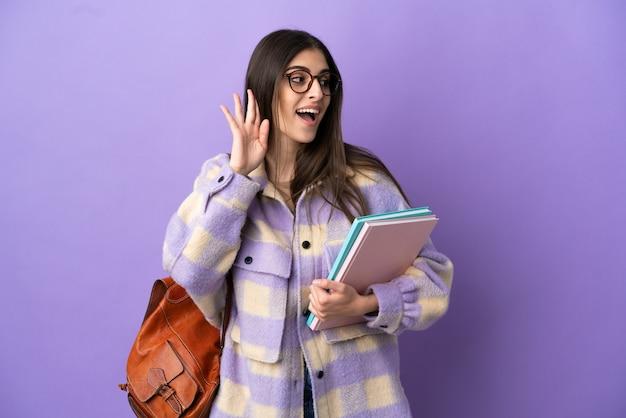 Молодая студентка женщина изолирована на фиолетовом фоне, слушая что-то, положив руку на ухо