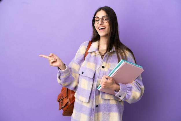 보라색 배경에 손가락을 옆으로 가리키는 젊은 학생 여성