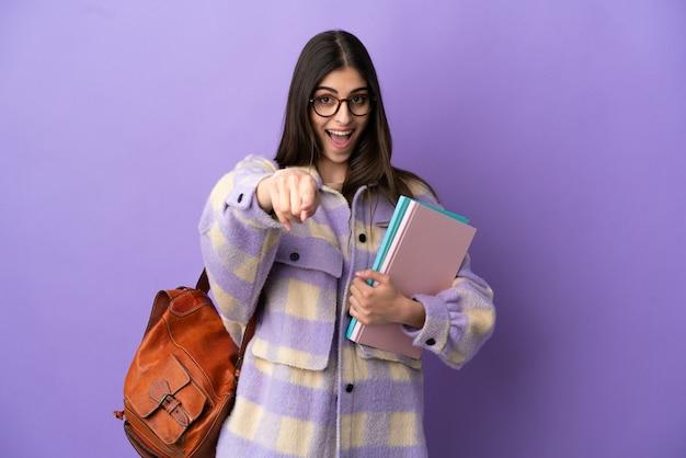 행복 한 표정으로 앞을 가리키는 보라색 배경에 고립 된 젊은 학생 여자