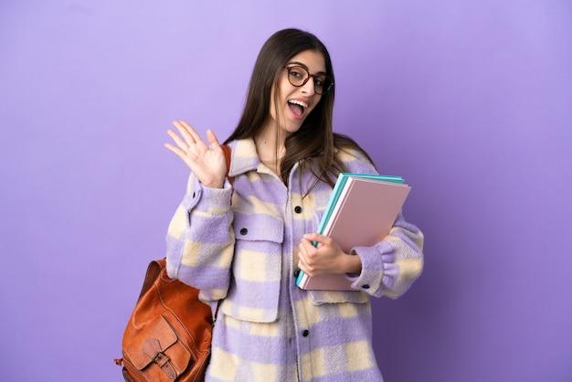 Молодая студентка женщина изолирована на фиолетовом фоне, салютуя рукой с счастливым выражением лица