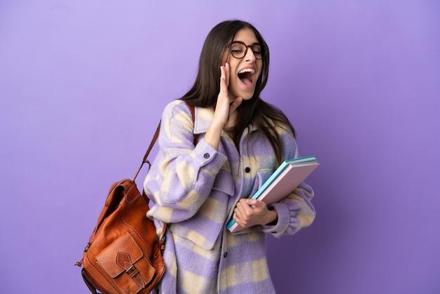 보라색 배경에 고립된 젊은 학생 여성이 입을 크게 벌리고 소리를 지른다