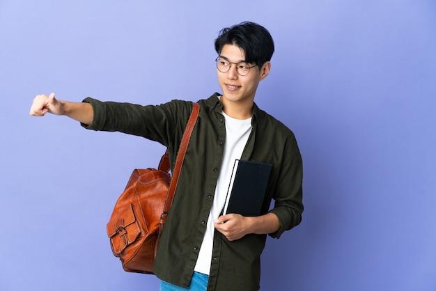 Молодая студентка изолирована на фиолетовой стене, показывая жест рукой вверх